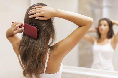 髪をブラシでとく女性1